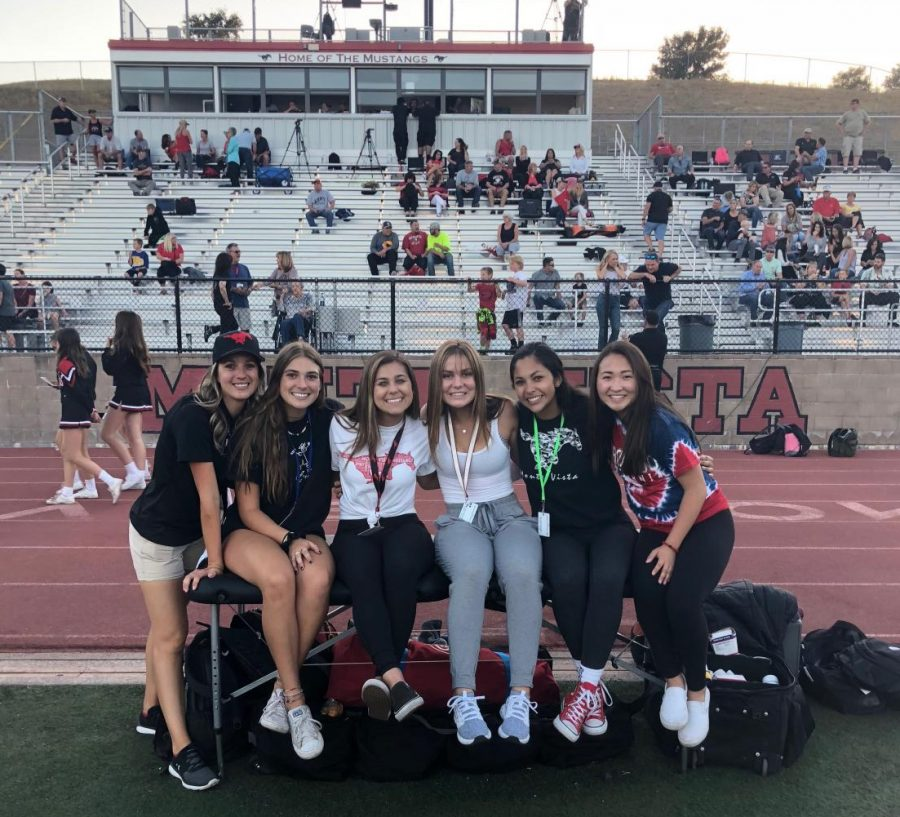 Student athletic trainers prepare for a football game. They helped players fill water bottles and Gatorade and assisted them with injuries.