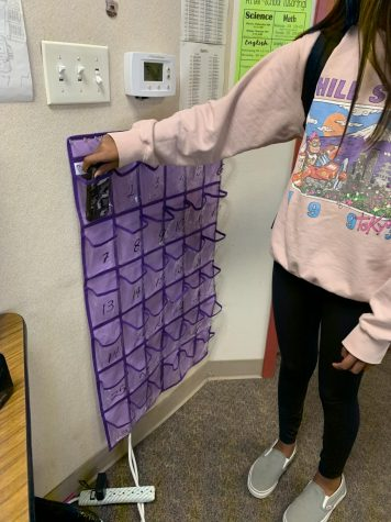 Freshman Avani Desai is putting her phone into the phone jail in Phoebe Roddewigs classroom before class starts.