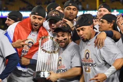 Houston Astros players hoist their trophy high in the air following their 2017 World Series Win. Players celebrate as they have just won their first-ever World Series, it would later come out that they cheated their way to becoming champions.