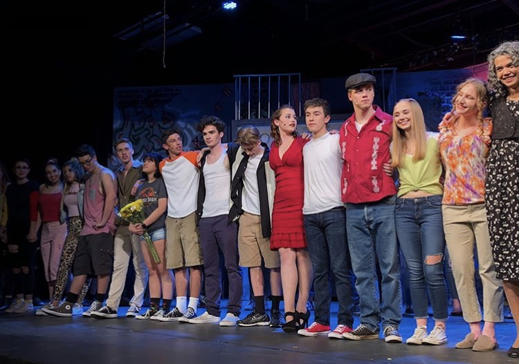 The entire cast lines up to take a final bow on closing night of their production,