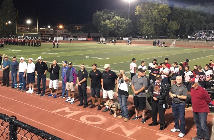 Over 15 veterans standing in front of the Monte Vista crowd. Many of the veterans have some association with Monte Vista.