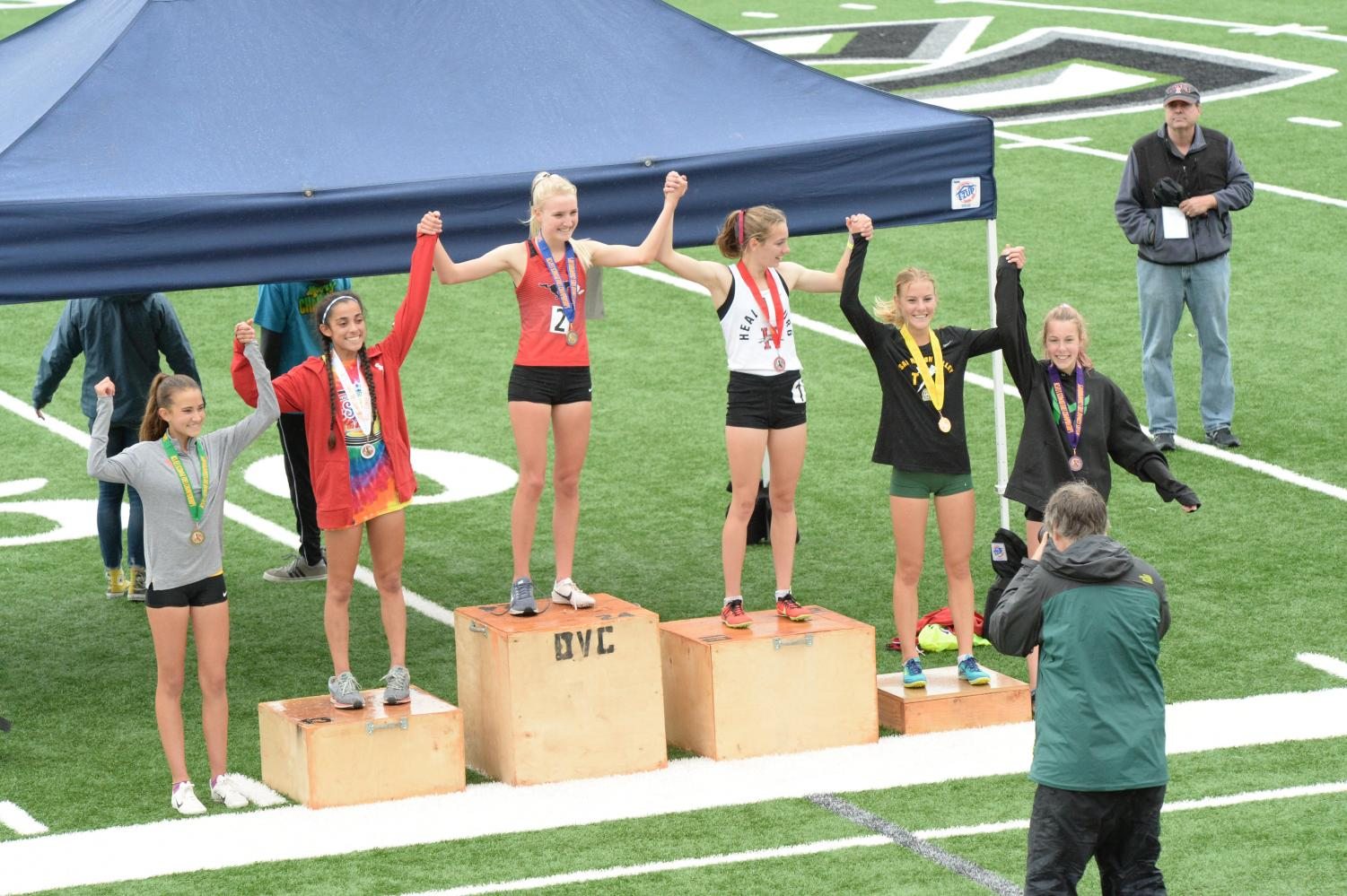 Senior Kelli Wilson stands in the middle of the podium, grinning as she wins NCS in the 3200-meter race. She committed to Duke University in October and will run for the cross country and track teams in the fall.