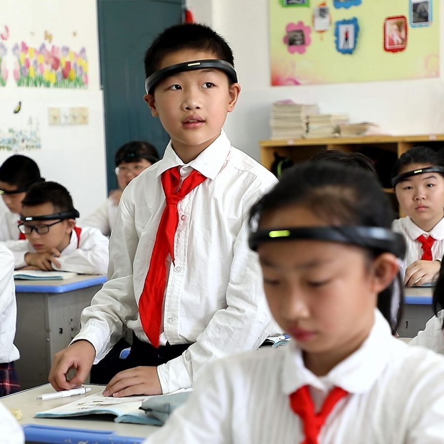 Chinese students wearing headwear that measures how well they are engaged with their teacher. China has been one of the world leaders in artificial intelligence and has pioneered how it is being used in classrooms and education as a whole.