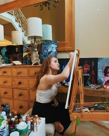 Senior Natalie Bennett poses among her portraits. Her paintings have reached millions of people through the popular video-sharing app, TikTok.