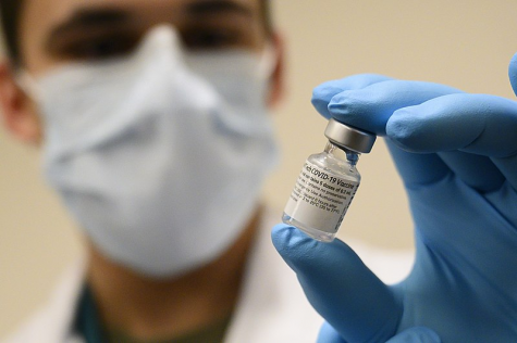 A U.S. Army Specialist prepares a vial of the Pfizer-BioNTech COVID-19 vaccine on Dec. 14, 2020, near the first phase of vaccinations for high-risk health workers and first responders.